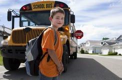 Travesía joven del muchacho delante del autobús escolar amarillo Foto de archivo