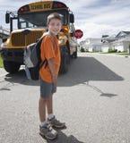 Travesía joven del muchacho delante del autobús escolar amarillo Fotos de archivo