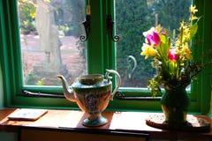 Travesaño adornado de la ventana con las flores en un florero y un jarro del té imagen de archivo