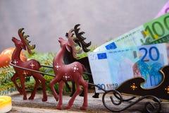Travesaño de la Navidad con el dinero en carro del reno Fotografía de archivo libre de regalías