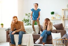 Travieso, dañoso, bebé el salto, la risa y divertirse, padres subrayaron con dolor de cabeza imagen de archivo