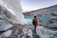 Travler novo que olha o lago azul da cratera em Kawah Ijen, Indonésia fotografia de stock royalty free