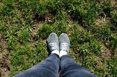 Trawa i nogi journeyer I?? na piechot? podr??nika Trawa Zielona trawa Gazon i cieki Zielony miasto Cajgi i sneakers Kapcie dla sp zdjęcie stock