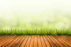 Trawa z zielenią zamazywał tła i drewna podłoga Zdjęcia Stock