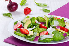 Trawberry, baby spinach, red onion, goat cheese and avocado salad on a white dish on a table mat. Strawberry, baby spinach, red onion, goat cheese and avocado stock photo
