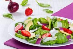 Trawberry behandla som ett barn spenat, den röda löken, getost och avokadosallad på en vit maträtt på ett underlägg Arkivfoto