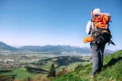 Traweler della donna con il soggiorno dello zaino sulla cima della collina Fotografia Stock