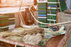 Trawl, pelagic boards, fishing net and boxes for fish lies on the fishery deck of a small fishing seiner.  stock photography