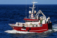 Trawler 1A. Fishing trawler underway at sea over blue sky and sea Stock Photos