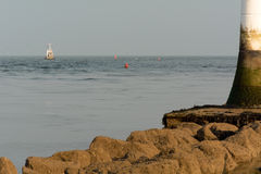 Trawler approaching small white lighthouse Royalty Free Stock Photo