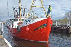 Trawler emerging from lock Stock Image