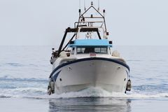 Trawler fishing boat approaching to port. Royalty Free Stock Photo