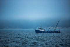 Trawler fishing boat sailing in open waters on a cold and foggy Royalty Free Stock Photos