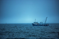 Trawler fishing boat sailing in open waters on a cold and foggy Royalty Free Stock Photography
