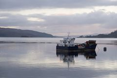 Trawler fishing boat at sunset on Loch Melfort Argyll west Scotland showing a calm peaceful scene stock photo