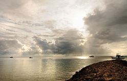 Trawler fishing boats and yacht in storm on silver sea. A stunning silvery seascape of a number of sea vessels moored on the sea in the harbor during a dangerous Royalty Free Stock Images