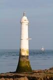 Trawler fishing in sea near small white lighthouse Royalty Free Stock Photos