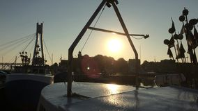 Trawler in the harbor in backlight. Ing in the morning wit sun reflexion stock footage