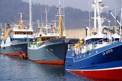 Trawler and longliners fishing boats docked in Celeiro harbor in Spain. Fishing boats docked in the fishing harbor of Celeiro after work all night in the coasts Royalty Free Stock Photos