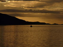A trawler returns, Loch Broom near Ullapool, Scotland. A trawler returns from a fishing trip in the tranquility of  a Loch Broom evening near Ullapool on the Royalty Free Stock Images