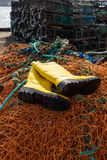 Trawlerman's protective boots, commercial fishing nets and lobster pots Stock Images