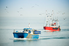 Trawlers. Fishing trawlers returning to port on a hazy day surrounded by seagulls Stock Photos