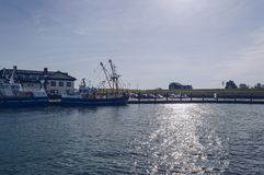 Trawlers and building in Oudeschild at Texel island. Fishing trawlers and buildings in Oudeschild port onTexel island on sunny october day stock photos