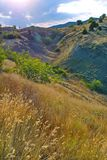 Trawy dorośnięcie na halnym skłonie obok małego wydrążenia między wzgórzami z wybitnym jaskrawym słońcem na niebieskim niebie zdjęcie stock