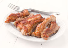 Tray with appetizing fried pork ribs white wooden Stock Image