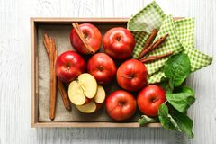 Tray with apples and cinnamon sticks. On wooden background Royalty Free Stock Photo