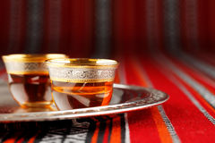 A tray of Arabian tea cups is placed on Arabian woven fabric Stock Photography