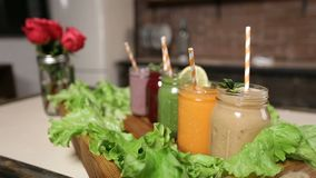 Tray with assortment of smoothies in jars. Vintage wooden tray decorated with green salad and different freshly blended vegetable and fruit smoothies in mason stock video