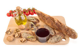 Tray with baguette, nuts, olives, oil, vine, tomatoes on white. Royalty Free Stock Image