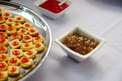 Tray of biscuits with cheee and red topping, lined up on metal plate Royalty Free Stock Photo