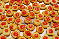 Tray of biscuits with cheee and red topping, lined up on metal surface Stock Image