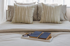 Tray of book with glass on bed in luxury bedroom Royalty Free Stock Image