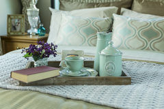 Tray with book,tea set and flower on the bed Stock Photo
