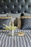 Tray of book with vase of  plant on bed in luxury black bedroom Stock Image