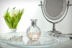 Tray with bottle of perfume. On table royalty free stock photo