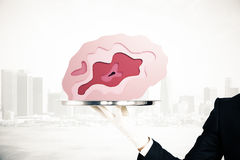 Tray with brain on city background. Hand in glove holding abstract brain placed on silver tray on city background. Brainstorming concept. 3D Rendering Stock Photos