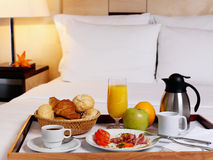 Tray with breakfast. On a bed in a hotel room Royalty Free Stock Photos