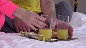Tray with breakfast on a bed, closeup. Tray with breakfast on a bed, happy morning together, orange juice and croissants, man dressed in gray pants and a white T stock video footage