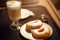On the tray is a Breakfast with a coffee drink and two donuts stock photography