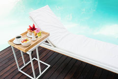 Tray with breakfast in side table and sun lounger Royalty Free Stock Image