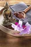 Tray with Buddha and orchid flowers for spirituality and massage. Buddha for spirituality at beauty spa with towel flower massage and ritual accessories for Royalty Free Stock Photos