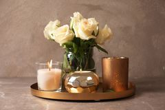 Tray with burning wax candles and flowers. On table royalty free stock photography