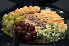 Tray of cheeses, grapes, seeds, bread. Royalty Free Stock Photography