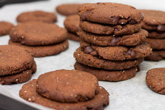 Tray of chocolate cacao chia seed cookies stacked on white parch stock image