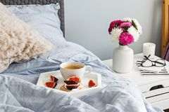 Tray with coffee and fig toast standing on the bed. Part of bedroom in the morning. Tray with coffee and fig toast standing on the bed royalty free stock photography