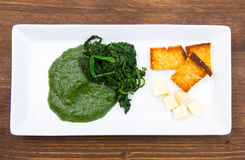 Tray with creamed spinach and croutons on wood from above Royalty Free Stock Photos